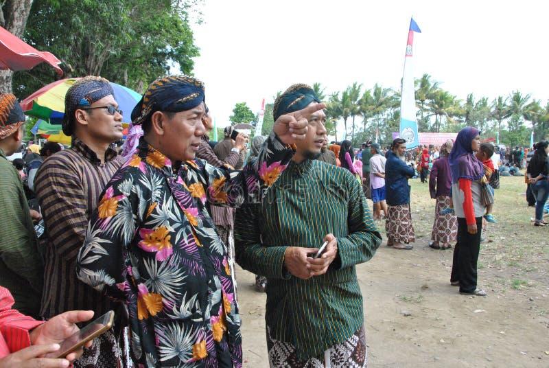 Um homem que esteja vestindo a roupa javanese está apontando a algo e a outro que procuram o fotografia de stock