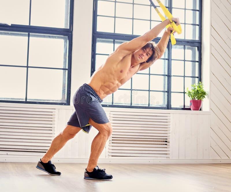 Um homem que faz exercícios com as correias do trx da suspensão foto de stock
