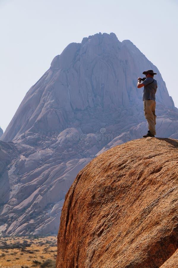Um homem que filma a paisagem no spitzkoppe foto de stock