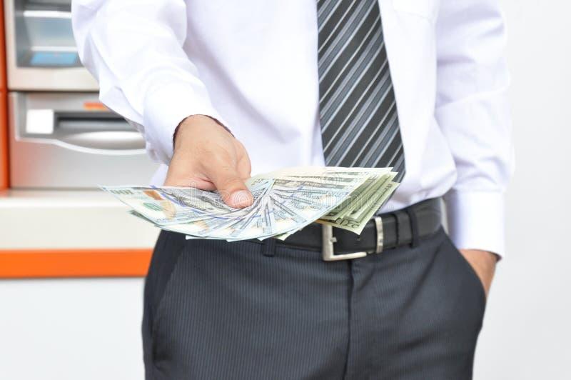 Um homem que guarda notas de dólar dos E.U. do dinheiro na frente do fundo do ATM imagens de stock royalty free