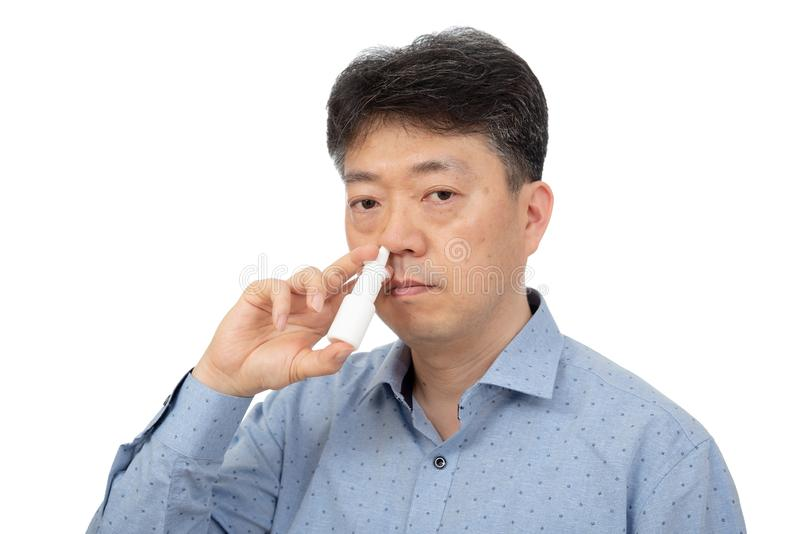 Um homem que guarda um pulverizador nasal em sua mão no fundo branco fotografia de stock royalty free