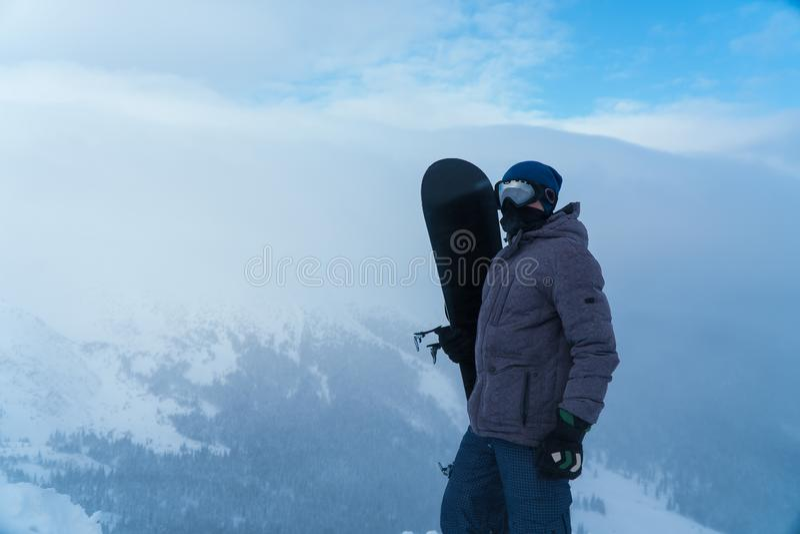Um homem que guarda um snowboard à disposição Snowboarder nas montanhas imagens de stock