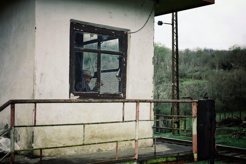 um homem que guarda uma estação de interruptor do trilho na parte montanhosa do país em sua estação que espreita fora da janela fotos de stock