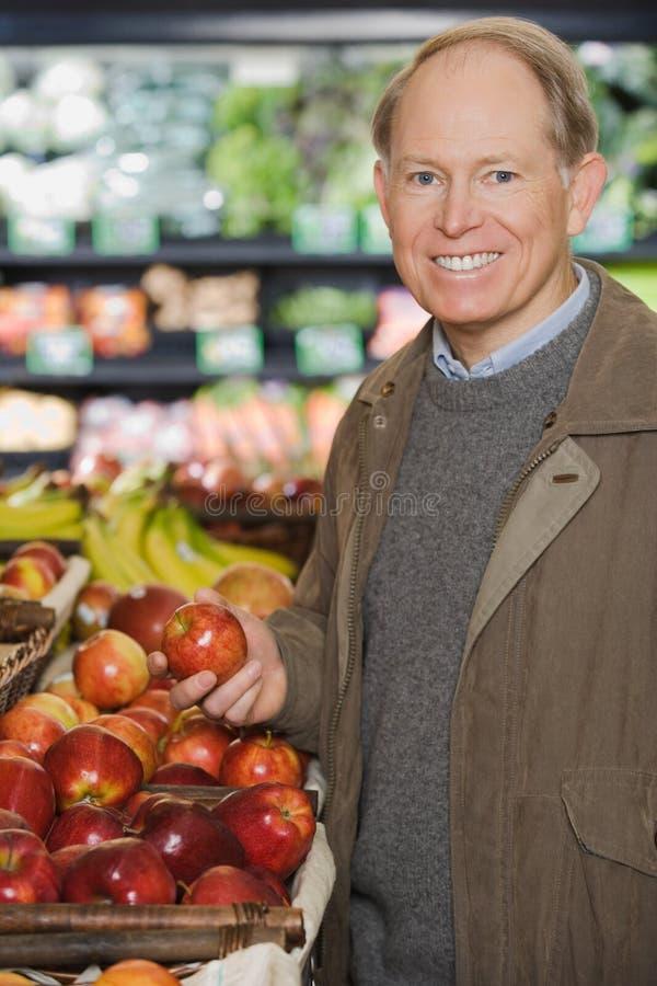 Um homem que guarda uma maçã fotografia de stock