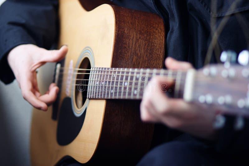 Um homem que joga a guitarra de madeira acústica da seis-corda foto de stock