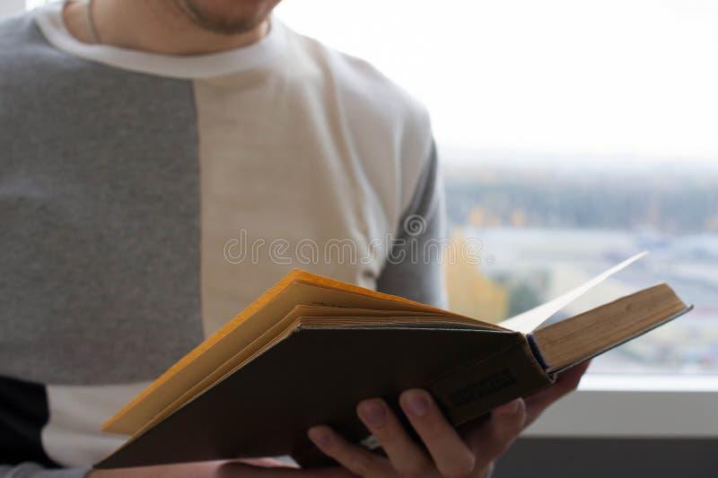 Um homem que lê um livro, posses ele em suas mãos fotografia de stock