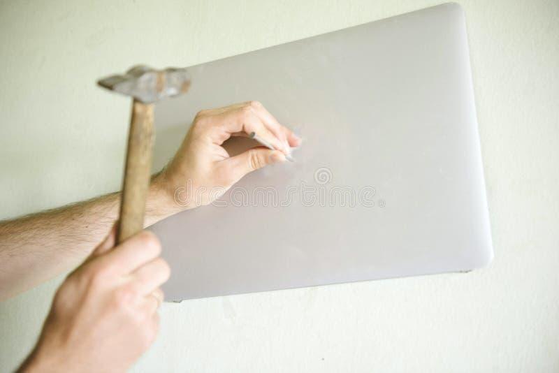 Um homem que martela um prego na tela de monitor fotos de stock royalty free