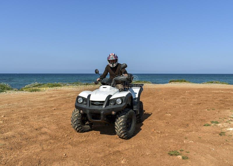 Um homem que monta ATV na areia em um capacete imagem de stock