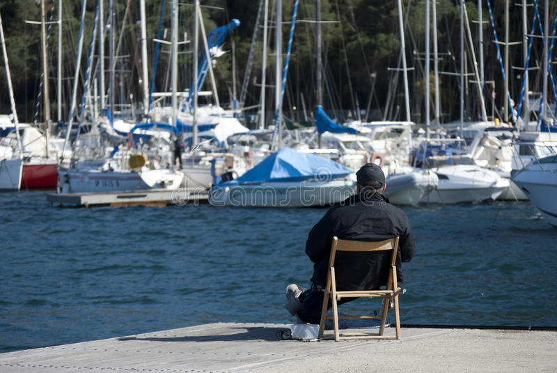 Um homem que olha barcos fotografia de stock