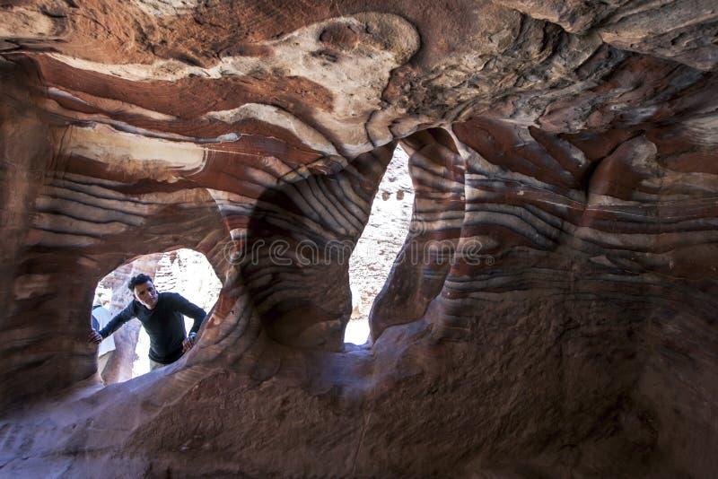 Um homem que olha o interior um do arenito do spectacular cava em PETRA em Jordânia imagem de stock
