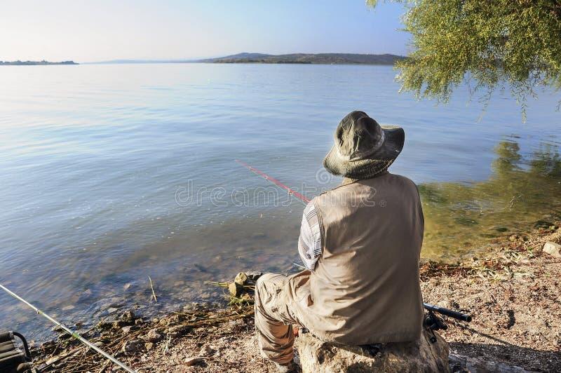 Um homem que pesca pelo lago no verão fotos de stock