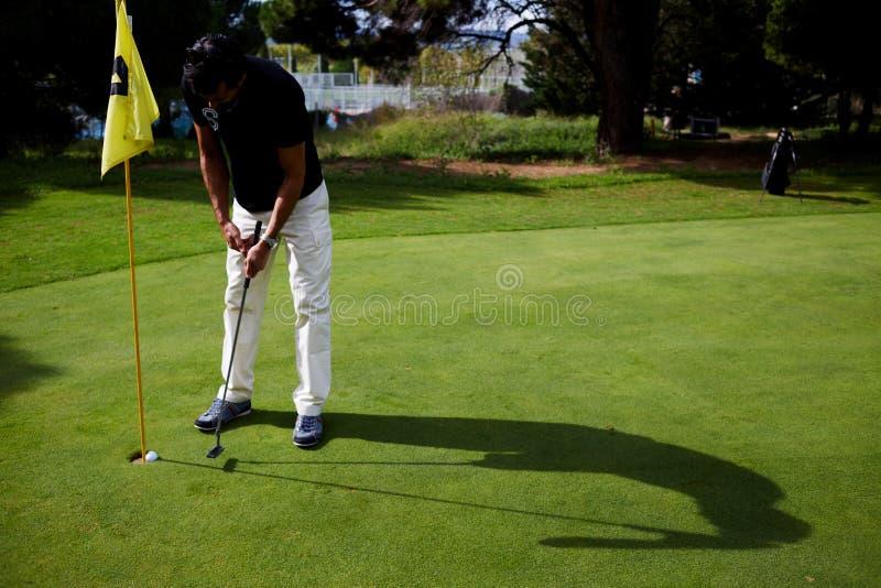 Um homem que prepara-se para golpear o campo de golfe fotos de stock