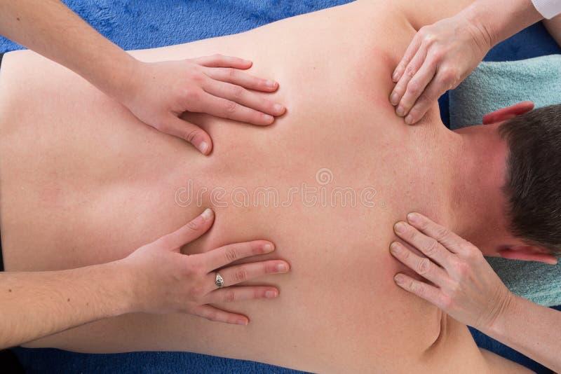 um homem que recebe uma massagem traseira em termas com as quatro mulheres das mãos foto de stock