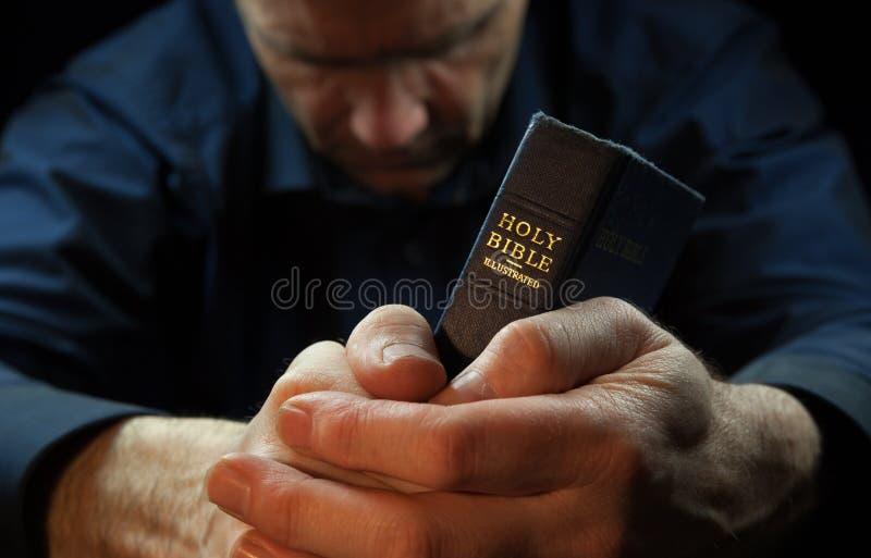 Um homem que reza guardarando uma Bíblia.