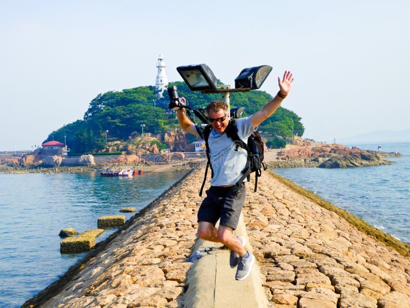 Um homem que salta na ponte de cavalete de Qingdao imagens de stock