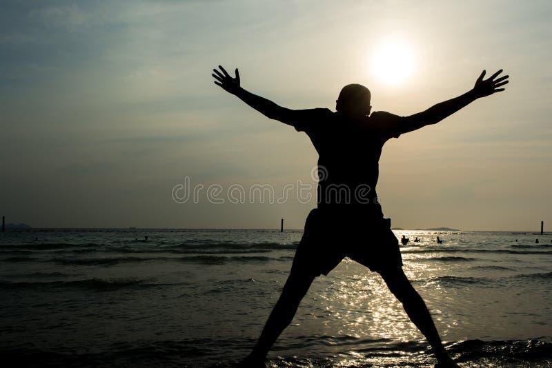 Um homem que salta no mar imagem de stock