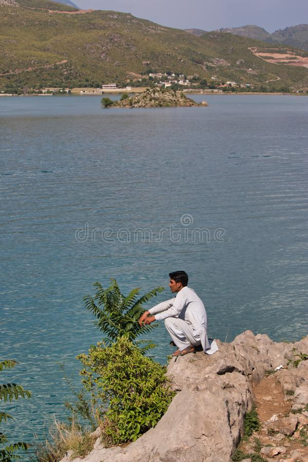 Um homem que senta-se ao lado do lago e que aprecia a vista imagens de stock