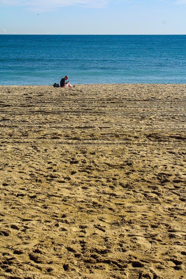 Um homem que senta-se apenas na praia imagens de stock royalty free