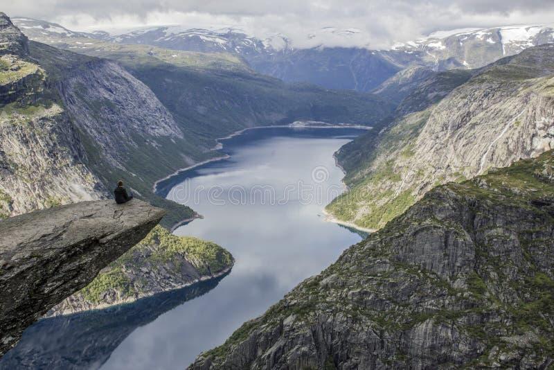 Um homem que senta-se na rocha da língua do ` s da pesca à corrica do trolltunga, Noruega imagens de stock