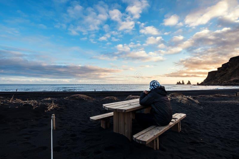 Um homem que senta-se no banco de madeira na praia preta da areia no por do sol fotos de stock
