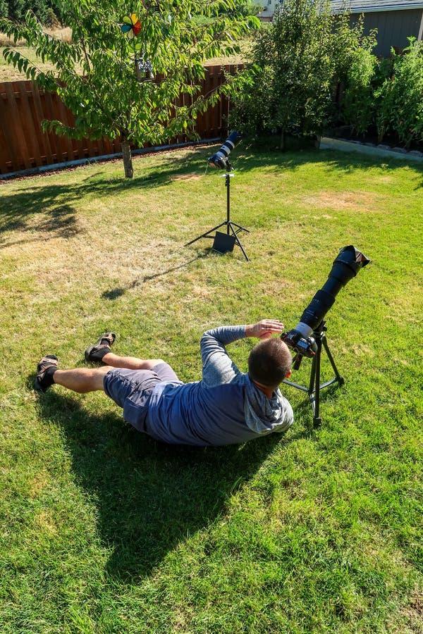Um homem que toma imagens de um eclipse solar total no quintal da casa o 21 de agosto de 2017 imagens de stock