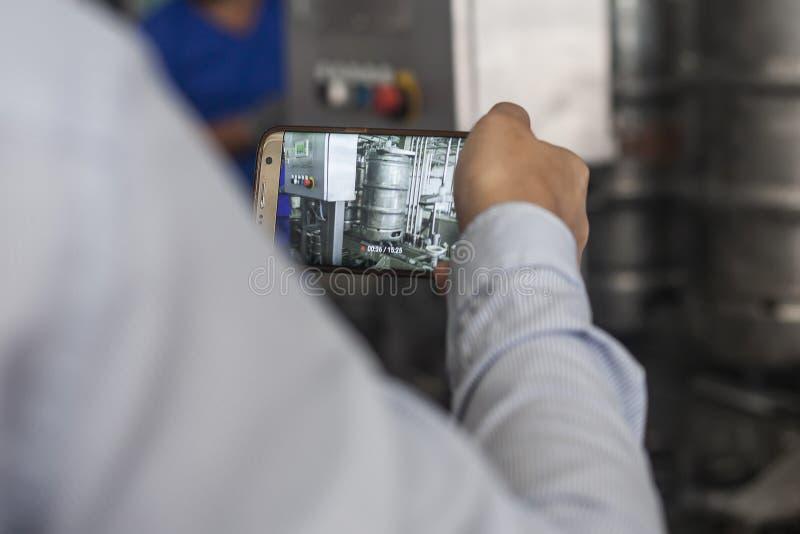Um homem que toma a vídeo com telefone celular o processo de fazer a cerveja fotos de stock