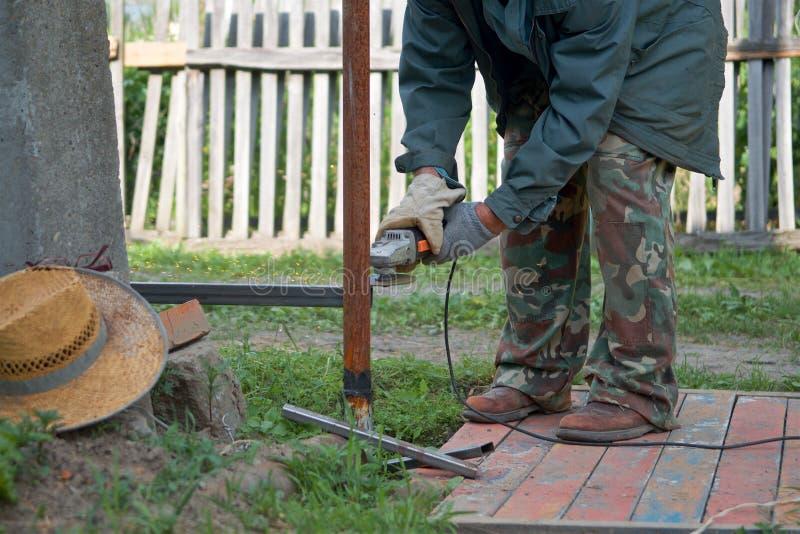 Um homem que trabalha com o moedor de ângulo no quintal fotografia de stock royalty free