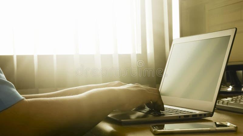 Um homem que trabalha em seu portátil imagens de stock