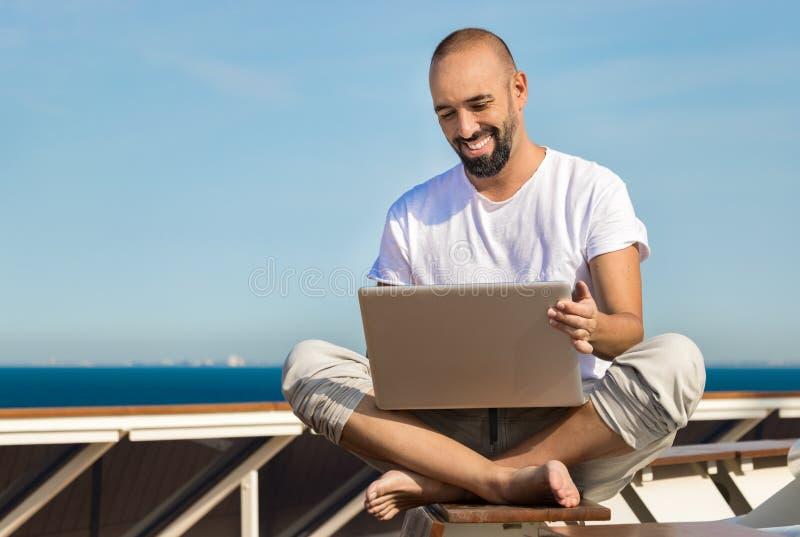 Um homem que usa seu portátil no mar em um iate fotografia de stock