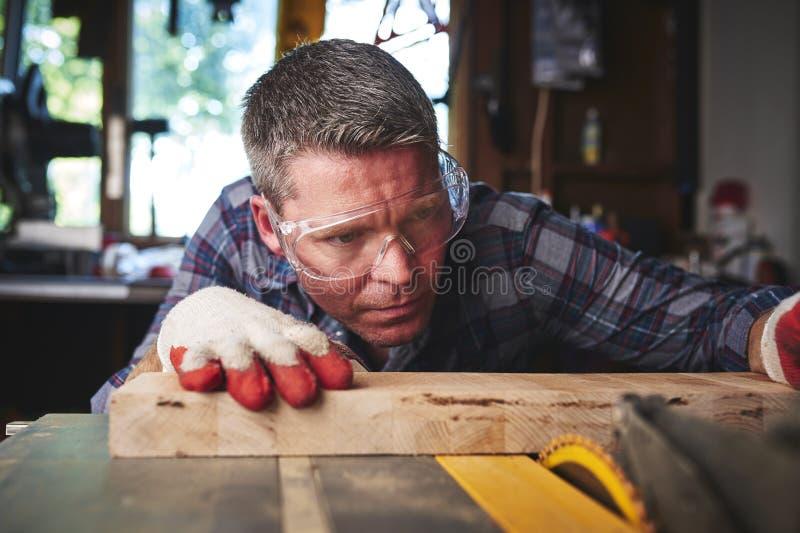 Um homem que usa uma serra da tabela foto de stock