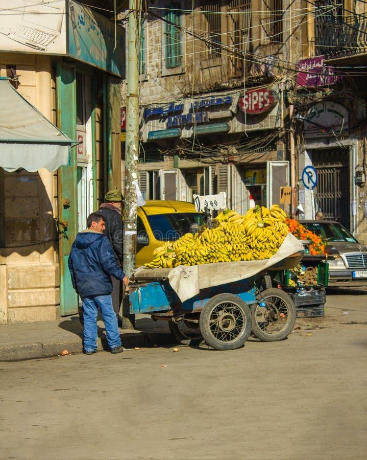 Um homem que vende bananas em um carro no Tripoli do centro, Líbano fotos de stock