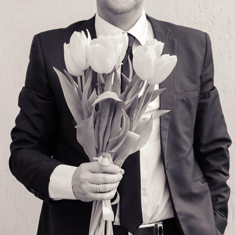 Um homem que veste um terno de negócio, guardando um ramalhete das tulipas O homem dá um ramalhete das flores fotografia de stock royalty free