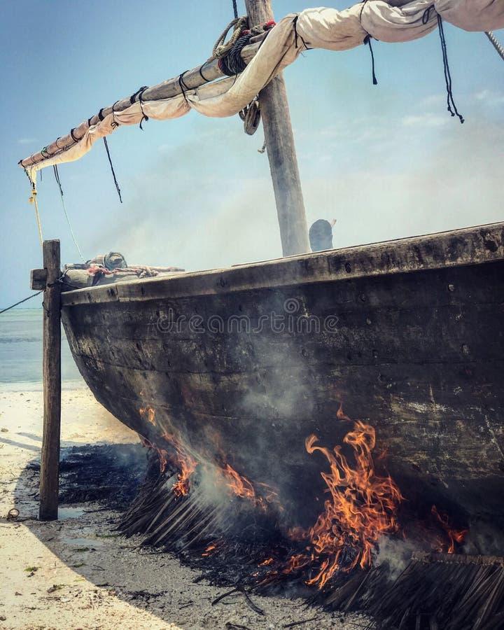 Um homem queima um dhow nas costas de Zanzibar, Tanzânia fotografia de stock royalty free