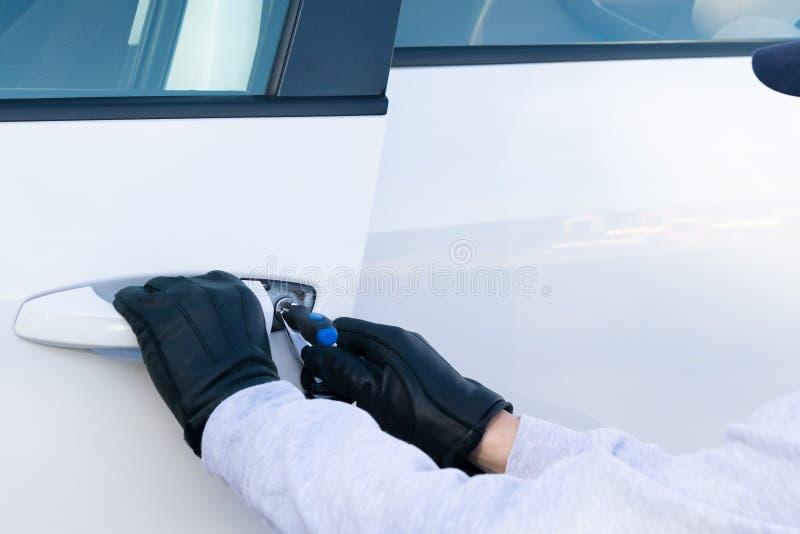 Um homem quer roubar um carro, ele destravou a porta com uma chave mestra, vista traseira imagem de stock royalty free