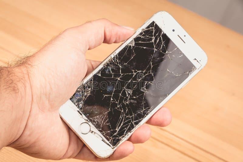 Um homem realiza em sua mão um iphone 6S de Apple Inc imagens de stock