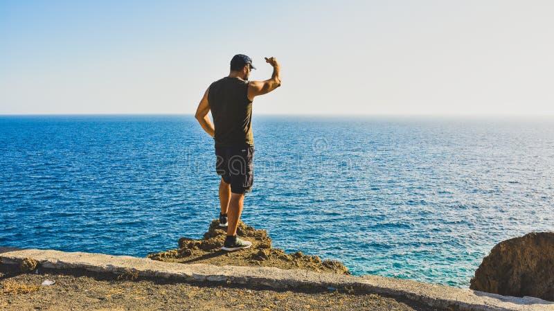 Um homem relaxa ao olhar o mar foto de stock royalty free