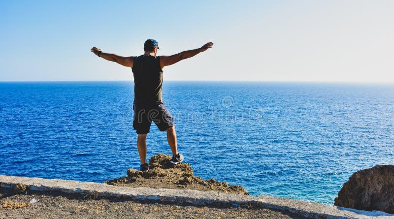 Um homem relaxa ao olhar o mar imagem de stock