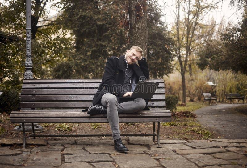 Um homem relaxado novo, sentando-se no parque do banco em p?blico, usando o port?til, fotos de stock
