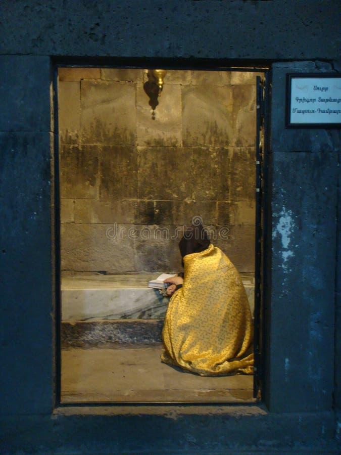 Um homem religioso sentado do ortodoxo armênio churchseen visto de trás que lido a Bíblia em uma pilha de um monastério de Armêni foto de stock royalty free