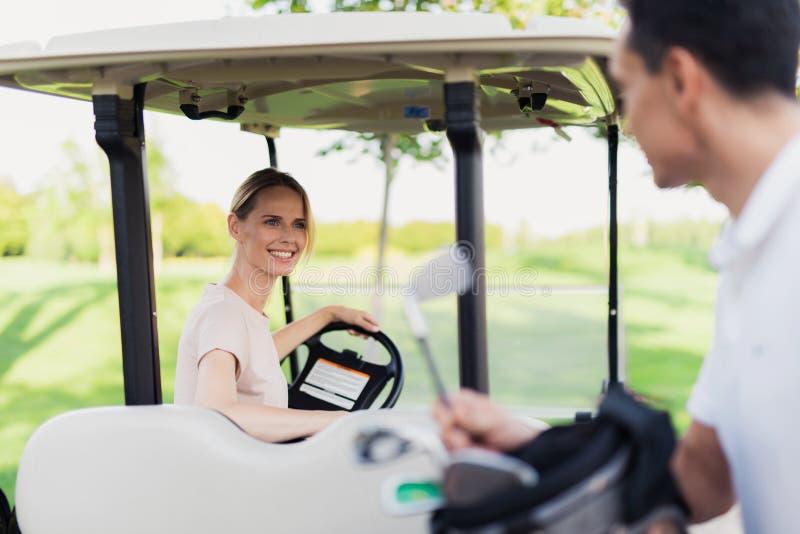 Um homem retira um clube de golfe do saco, uma mulher senta-se atrás da roda de um carro do golfe fotos de stock royalty free