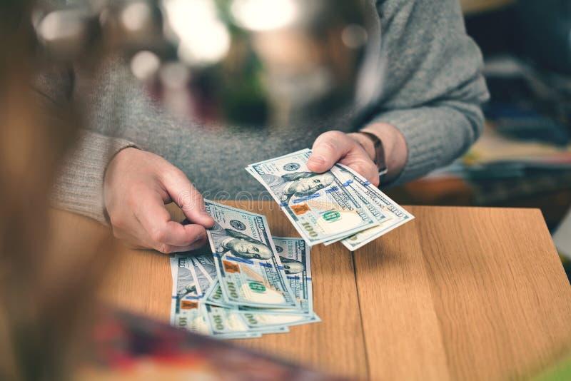 Um homem rico conta dólares as mãos e 100 notas de dólar fecham-se acima fotografia de stock