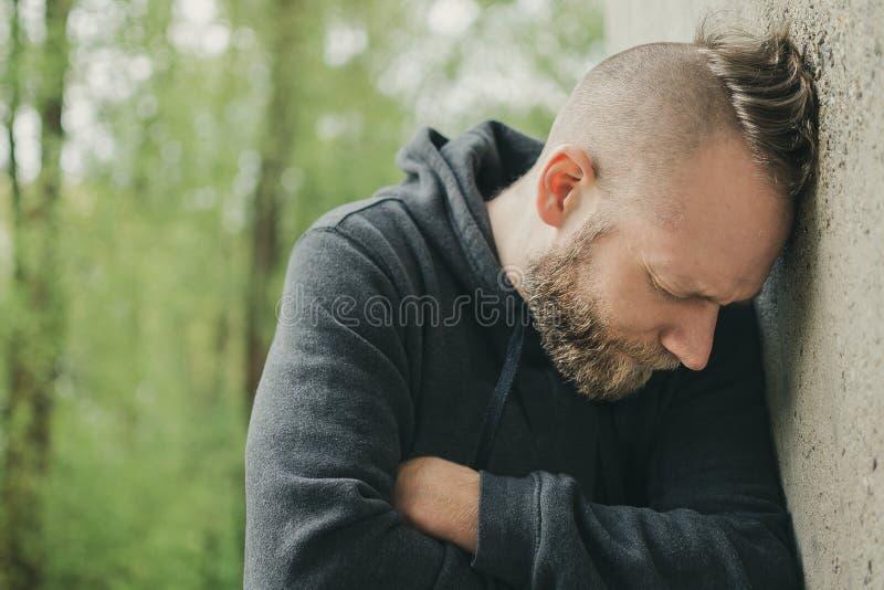 Um homem só e triste na parede foto de stock