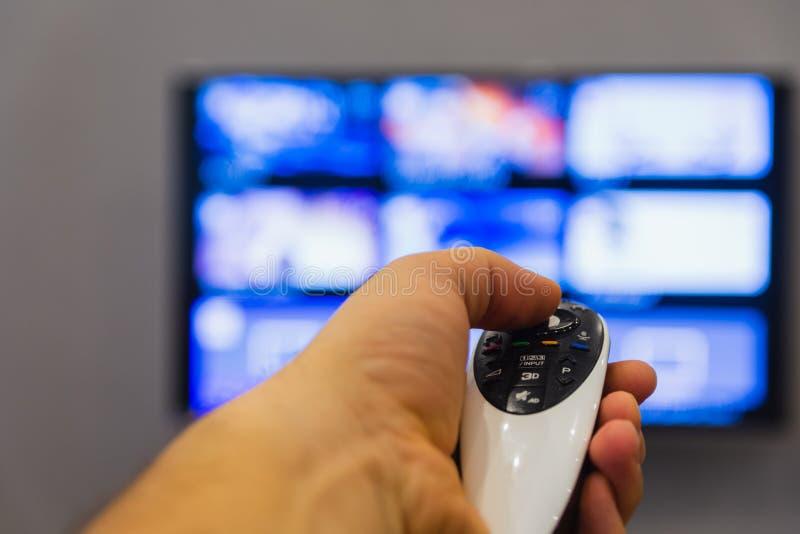 Um homem segura o controle remoto da TV manual fotos de stock royalty free