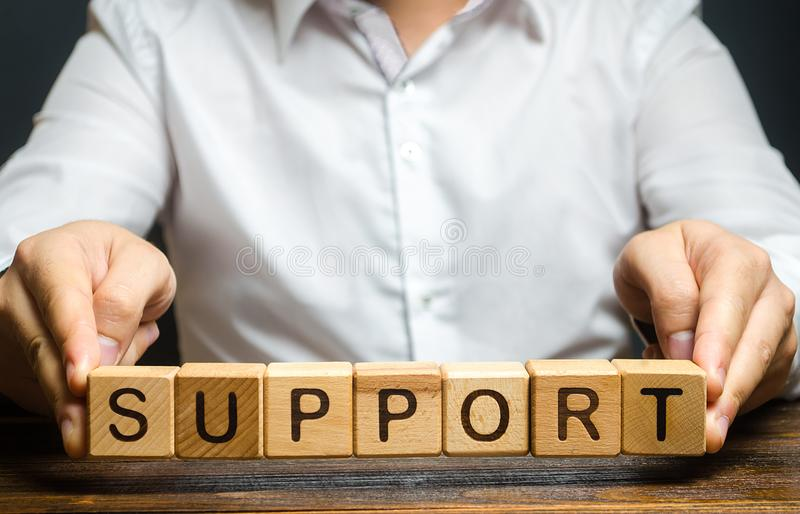Um homem segura a palavra Suporte Prestação de assistência e apoio às empresas em todas as fases do desenvolvimento da empresa Fi foto de stock