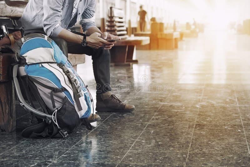 Um homem senta-se com mapa saco do curso no estação de caminhos-de-ferro imagens de stock