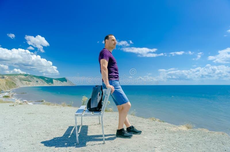 Um homem senta-se em um banco e em olhar o mar imagem de stock royalty free