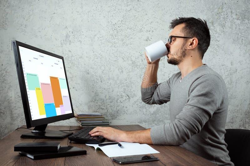 Um homem, um homem senta-se em uma tabela no escritório e no café das bebidas, uma ruptura Conceito para o trabalho de escritório imagem de stock