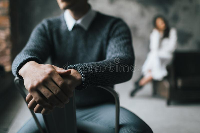 Um homem senta-se na cadeira em um fundo borrado de sua mulher Foco seletivo nas mãos do ` s do homem artwork fotos de stock royalty free