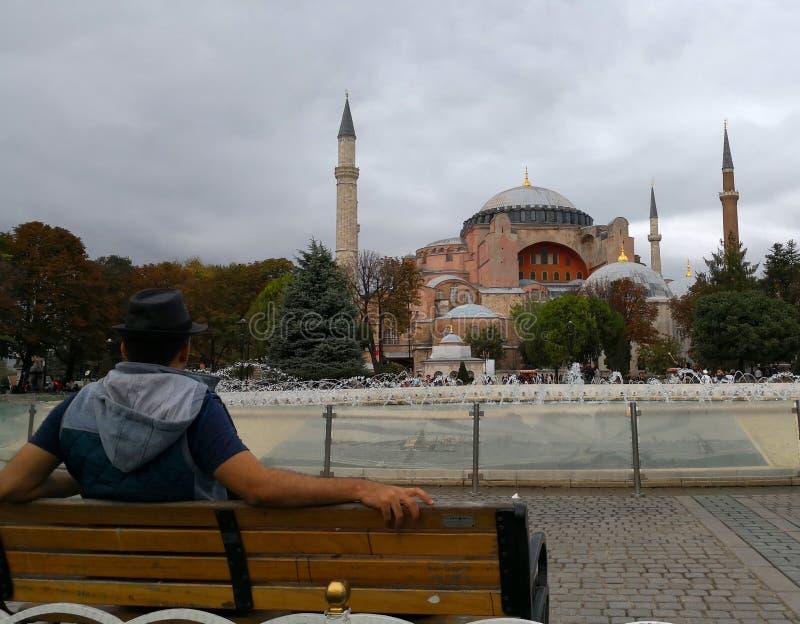 Um homem senta-se no banco e nos olhares na mesquita de Hagia Sophia foto de stock royalty free