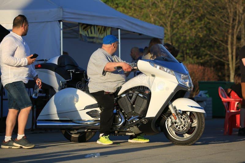 Um homem sentado numa mota branca, Victory Vision Tour numa noite ensolarada foto de stock